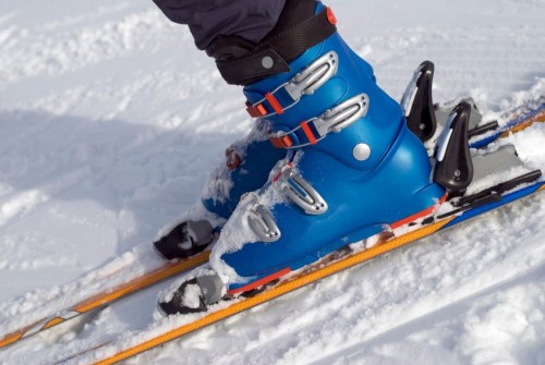 a pair of blue ski boots securely fastened to the skis.