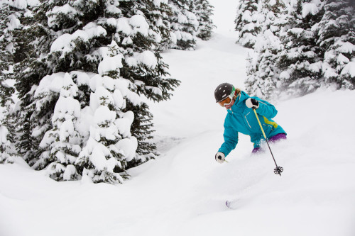 Person skiing on a powder day near the Limelight Hotel Aspen.