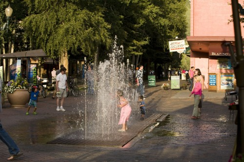 Little girl playing in the fountains in downtown Aspen near the Limelight Hotel Aspen.