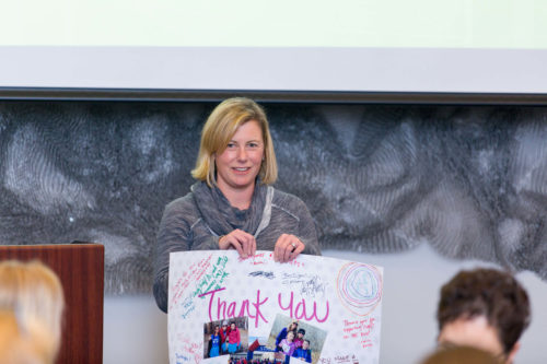 Woman holding a thank you card at the Limelight Ketchum community fund.