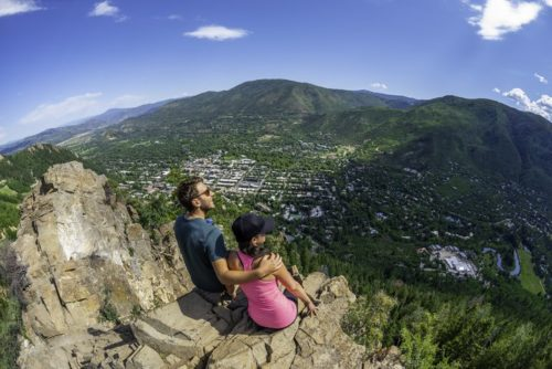 A couple overlooking a ski village in the summer near the Limelight Hotel.