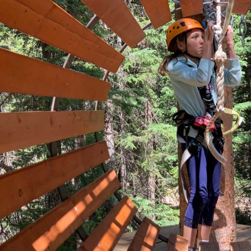 A girl playing at the Lost Forest adventure park near the Limelight Hotel Snowmass.
