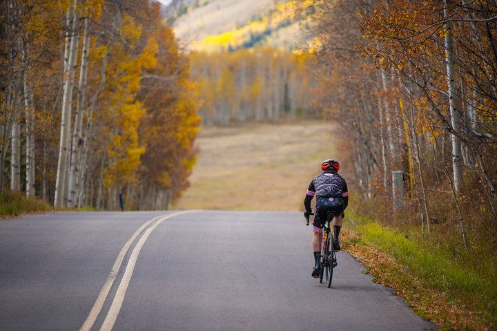 Shoulder Sesason in Mountain Towns - Biking down a mountain road with fall colors