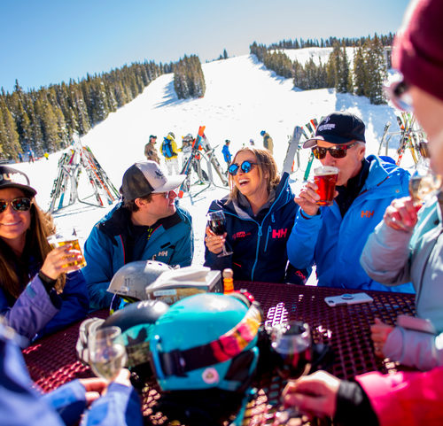 Best On-Mountain Dining Spots - A group of skiers enjoying a drink together