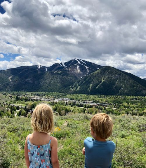 Young children looking at the view of the ski area near the Limelight Ketchum Hotel.